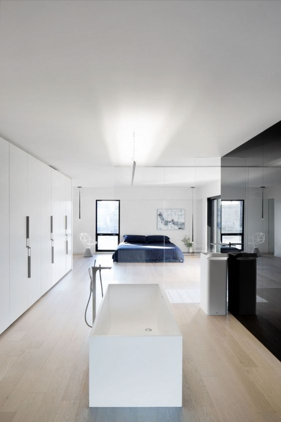 a minimalist spacious bedroom with a white free-standing bathtub and a sink separated only with a glass space divider