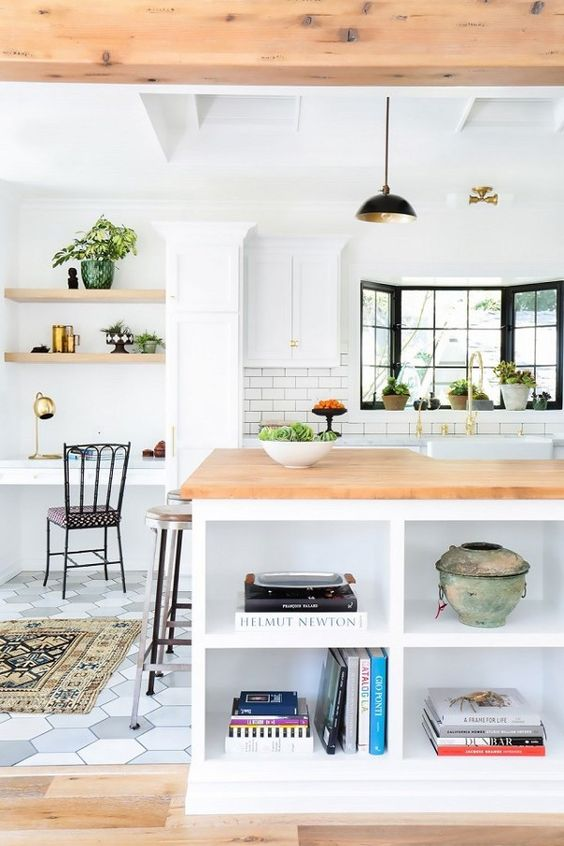 a modern farmhouse kitchen with a small home office nook by the window, with built-in shelves and a desk