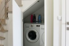 20 a small laundry with a washing machine and a dryer and with doors