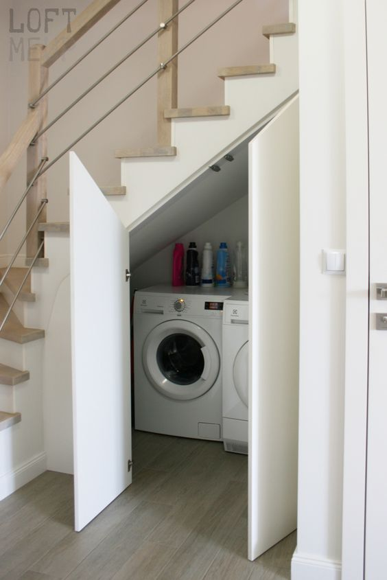 a small laundry with a washing machine and a dryer and with doors