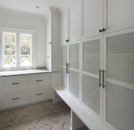 a white laundry room with all the stuff covered with wood lettice doors creates a perfect uncluttered look