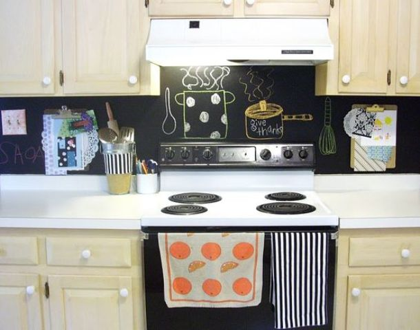 an ivory kitchen with white countertops and a chalkboard backsplash for a contrasting look