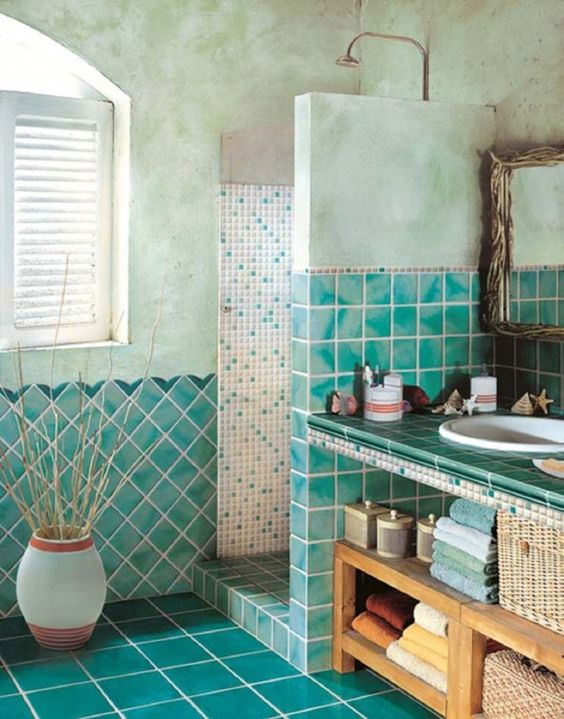 analogous bathroom with textural and watercolor turquoise tiles cover the walls and the shower and sleek glossy ones are covering the floor
