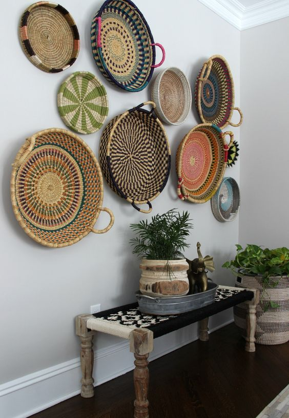 a boho woven and wooden bench, an arrangement of colorful baskets and basket planters