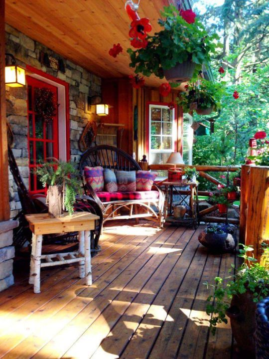 a colorful rustic boho porch with bright printed textiles, hanging plants and greenery and rattan furniture