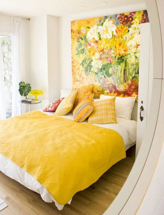 a colorful statement wall with an oversized artwork and matching pillows and a bedspread for summer