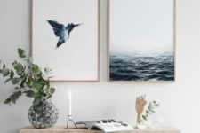 21 a modern beachy space with a wooden bench, sea-inspired artworks, pillows and vases