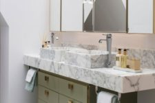 21 a muted green sink stand with gold knobs and a white marble vanity plus sinks create a luxurious combo