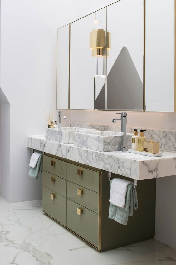 a muted green sink stand with gold knobs and a white marble vanity plus sinks create a luxurious combo