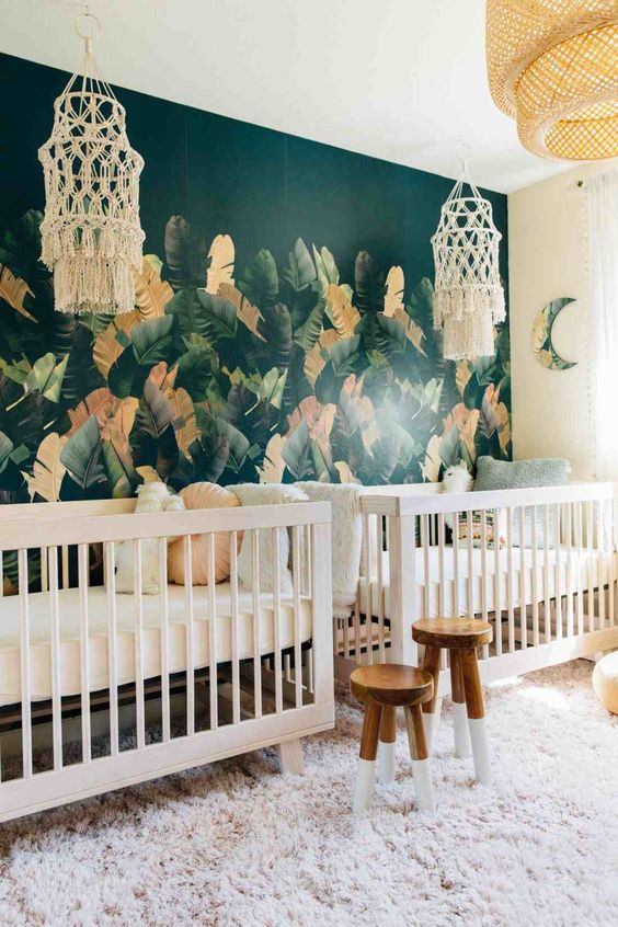 a shared boho tropical nursery with macrame chandeliers, cribs, stools and a faux fur rug plus a statement torpical leaf wall