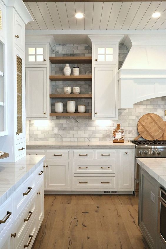 a traditional white kitchen with grey marble subway tiles on the backsplash and walls plus wooden touches