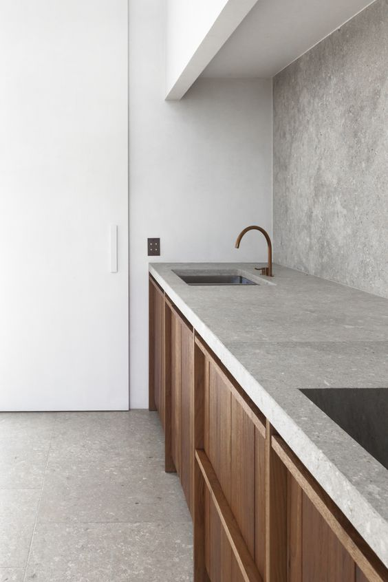 a two toned modern kitchen in white with a concrete backsplash and countertops