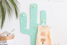 22 a colorful cactus decoration with hooks for hanging clothes an other stuff in a kid's room