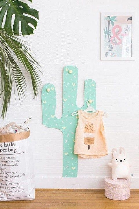 a colorful cactus decoration with hooks for hanging clothes an other stuff in a kid's room
