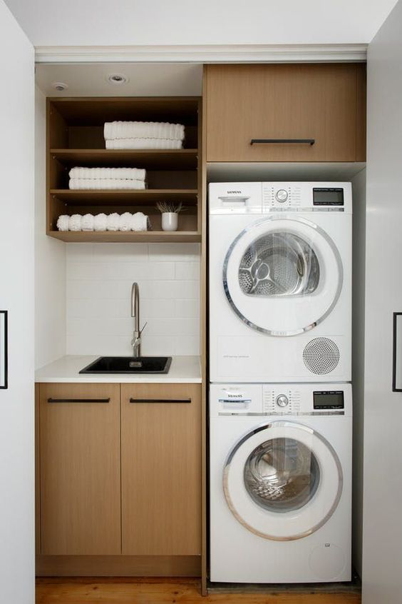 a comfy laundry under the stairs with a washing machine, a dryer, built in cabinets and even a sink