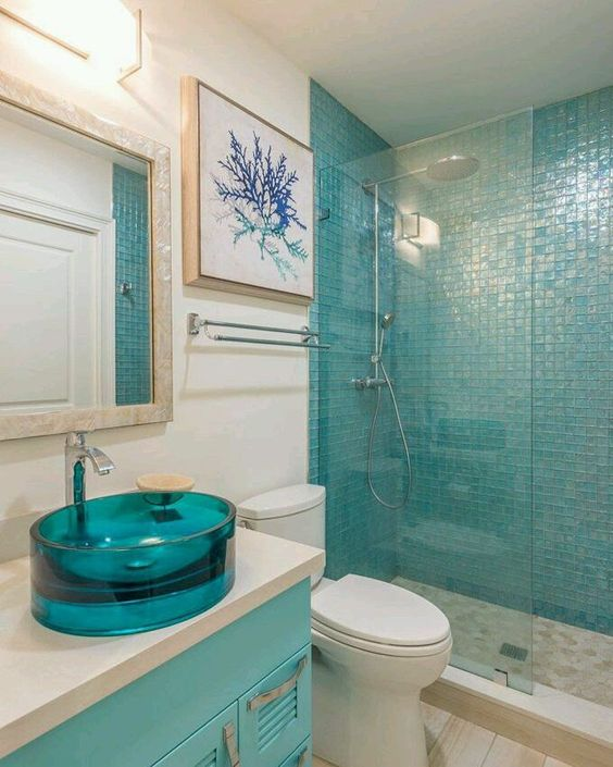 a glass turquoise round sink makes a colorful and stylish statement in the sea-inspired space