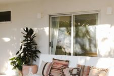 22 a gorgeous boho porch with an upholstered sofa, a raw edge side table, wicker ottomans and potted greenery
