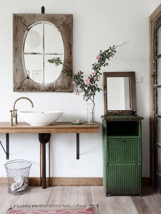 a green cabinet, a wood clad mirror, a wooden vanity and a a vintage faucet