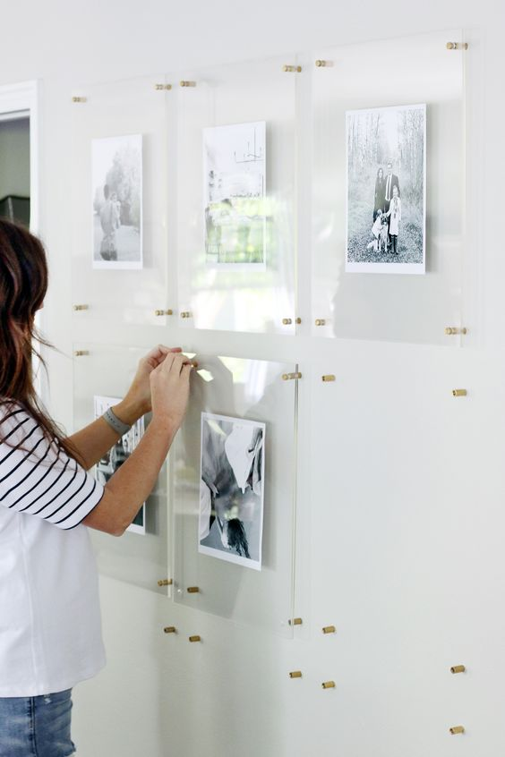 a modern floating gallery wall with family pictures in acrylic frames