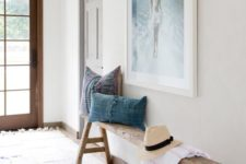 22 a reclaimed wood bench with trestle legs, chambray pillows, a sea-inspired artwork over the bench