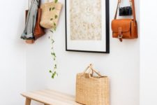 22 a simple wooden bench, a metal basket, an artwork, a cascading plant and a vintage camera