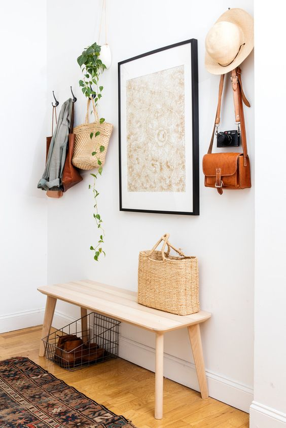 a simple wooden bench, a metal basket, an artwork, a cascading plant and a vintage camera