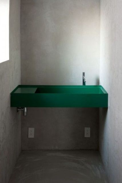 a small industrial powder room is spruced up with a minimalist emerald sink built-in between the walls