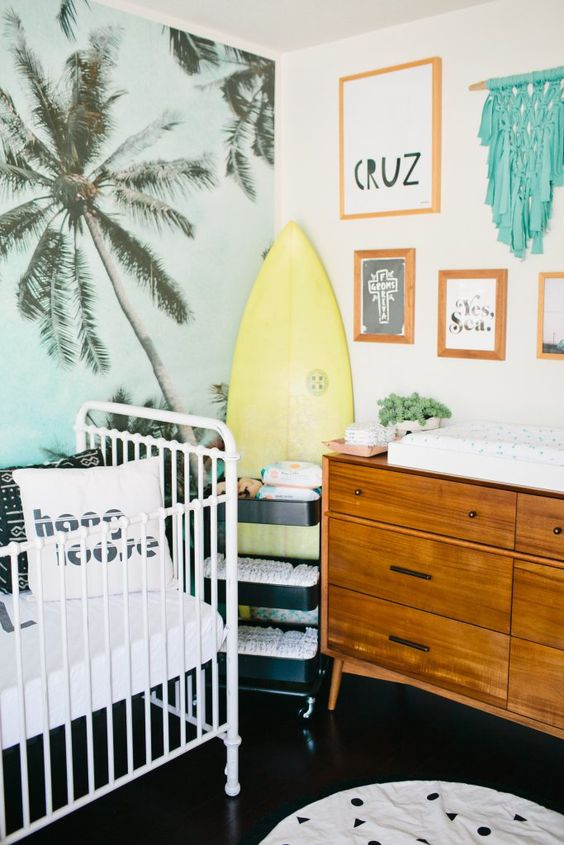 a tropical space with a surf, a blue palm print statement wall and colorful textiles