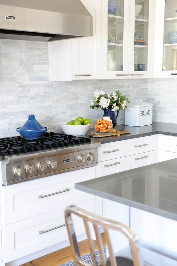 a white kitchen with grey countertops and a grey marble tile backsplash for a fresh modern look