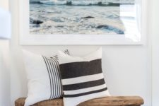 23 a simple beachy entryway with a wooden bench, a basket, a sea artwork and striped pillows