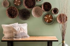 23 a wood and metal bench, woven and fringe pillows, an arrangement of plates and some branches