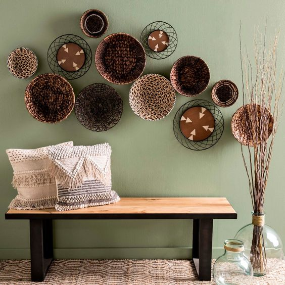 a wood and metal bench, woven and fringe pillows, an arrangement of plates and some branches