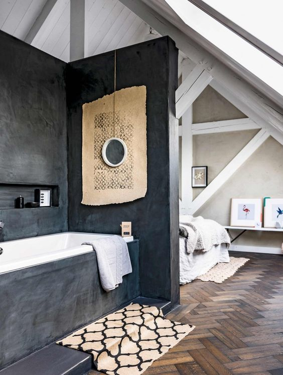 an attic bedroom with a bathtub zone separated with dark concrete from all the sides