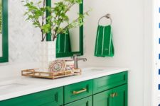 23 an emerald sink stand and framed mirrors add color to the space and are spruced up with brass touches