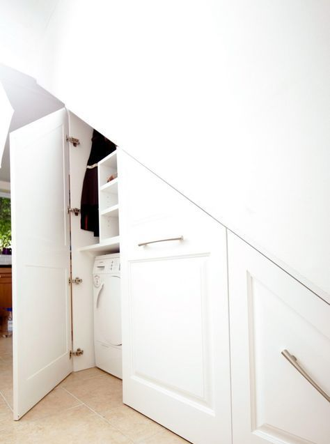 a built-in laundry space under the stairs with much storage for the things