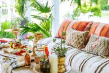 24 a super colorful boho porch with bold printed textiles, a pallet side table, greenery in pots and woven lanterns