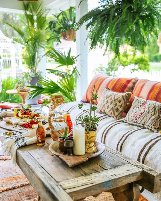 a super colorful boho porch with bold printed textiles, a pallet side table, greenery in pots and woven lanterns