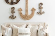 24 a vintage bench with drawers, embroidered pillows, a lantern and an arrangement of rope and driftwood anchors on the wall