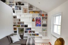 24 bookshelves built in into the wall and staircase for saving space in a small living room
