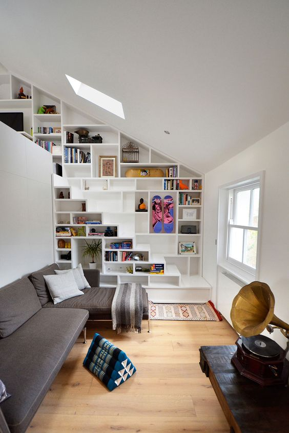 bookshelves built in into the wall and staircase for saving space in a small living room