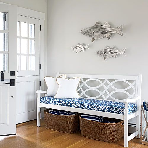 a vintage upholstered bench, baskets for storage and a wooden fish arrangement for decor