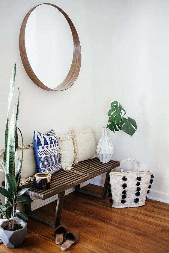 a wooden bench, a wood framed mirror, potted succulents and tropical leaves