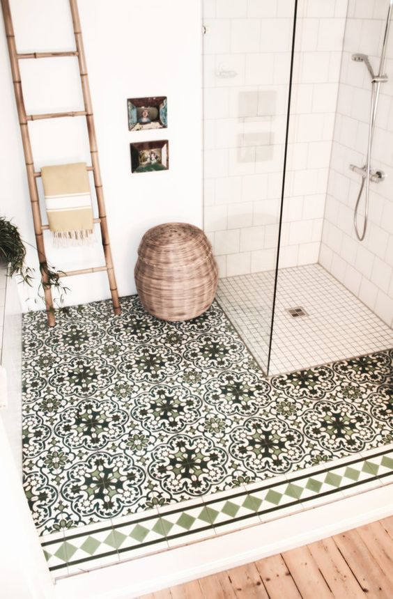 a wooden floor, a ladder as a towel rack, a basket for storage and mosaic tiles on the floor