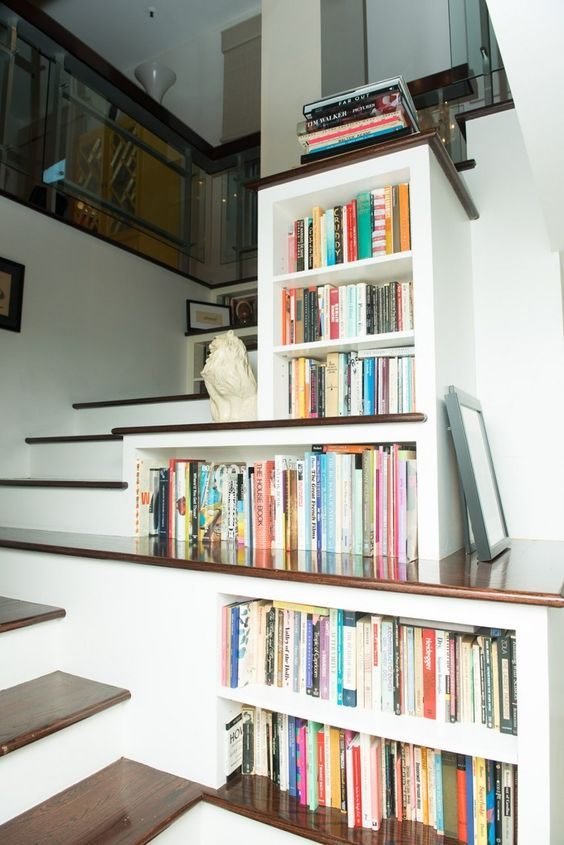 bookshelves built in right into the staircase to use every inch of space