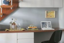 25 sleek storage cabinets on the wall and down on the floor, and a desktop that rests on them
