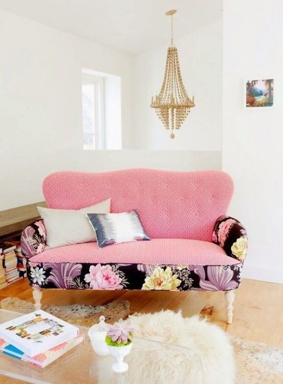 a cute pink loveseat with bright floral base and armrests to make it less boring