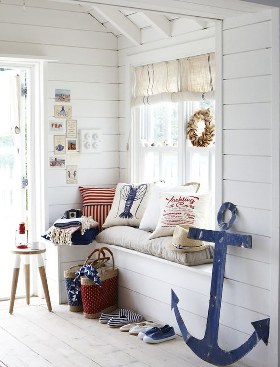 a whitewashed beach entryway with a windowsill bench, a stool, a shell wreath and some printed pillows