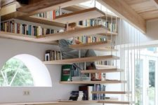 26 bookshelves covering the wall and under the space under the stairs is an effective solution