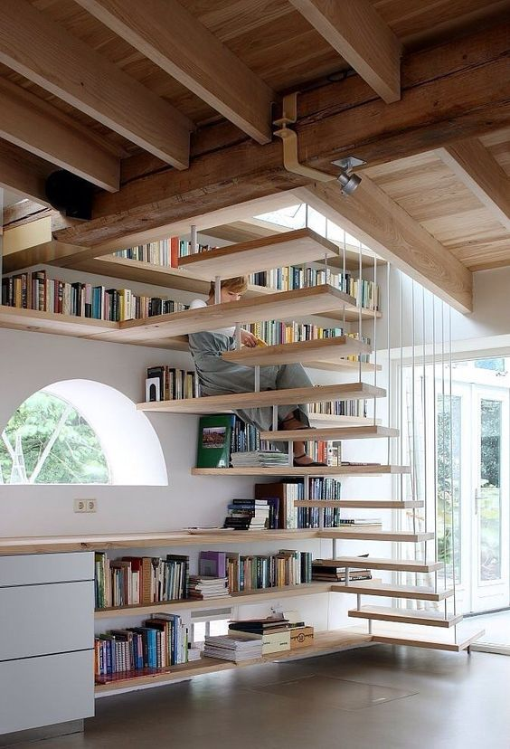bookshelves covering the wall and under the space under the stairs is an effective solution