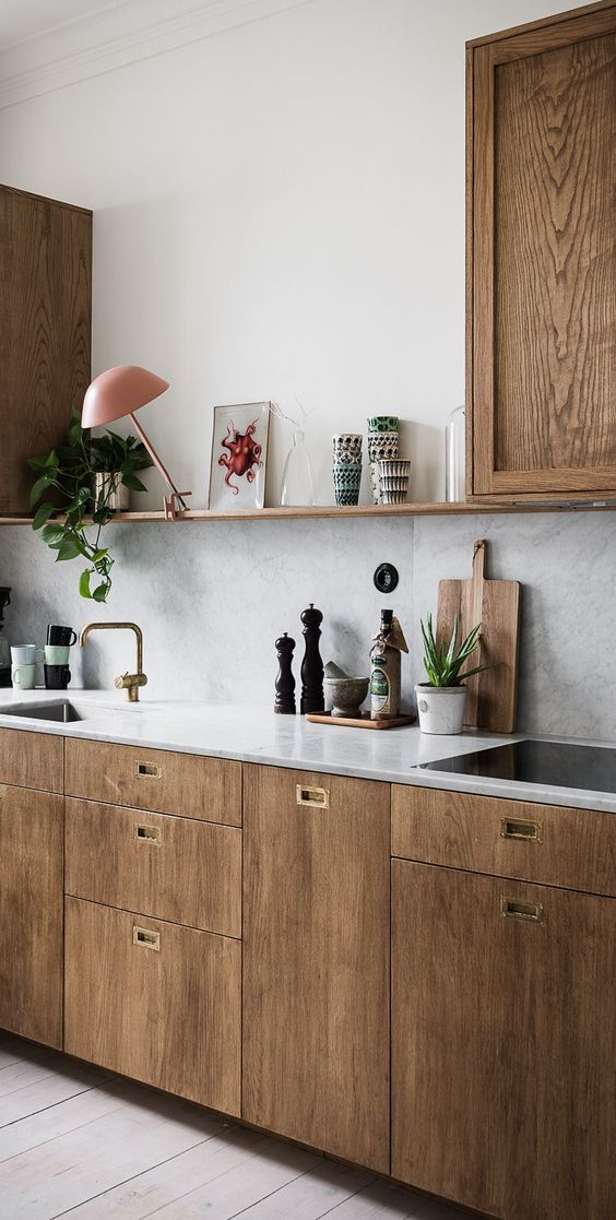 rich-colored wooden cabinets with grey marble tiles for the backsplash and countertops